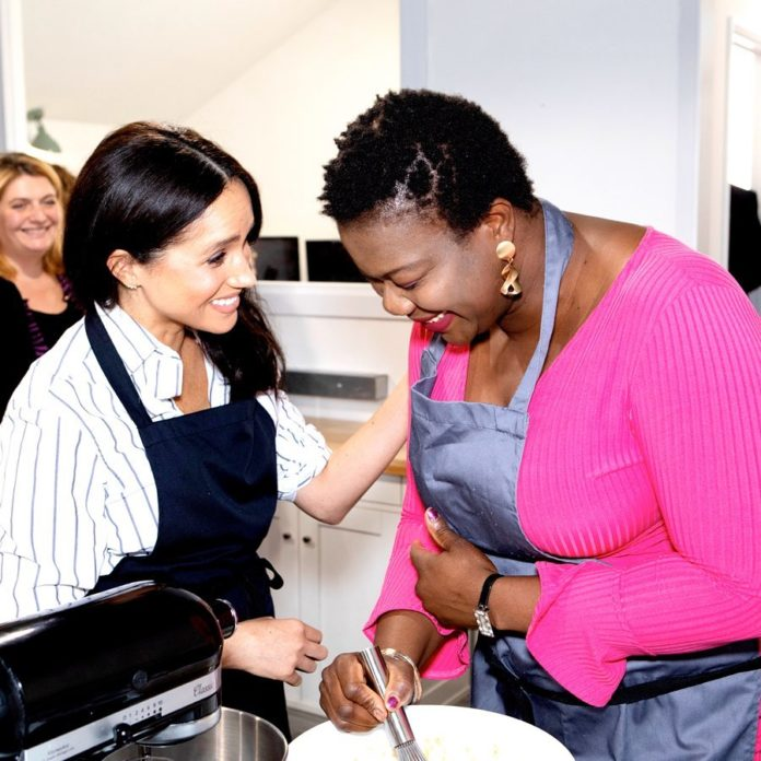 Meghan Markle interacting with one of the women at Luminary Bakery.